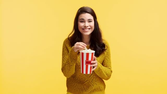 vídeos de stock, filmes e b-roll de menina de riso na camisola que come a pipoca isolada no amarelo - balde pipoca