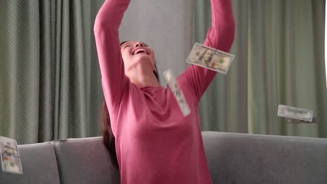 laughing girl sits on sofa under banknotes rain slow motion