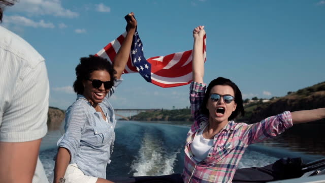 Laughing girls riding in a speedboat with flag Slow motion of diverse laughing girls friends wearing sunglasses holding American flag riding in a speedboat on a lake or river as they celebrate their summer vacation viewed close up. jetty stock videos & royalty-free footage