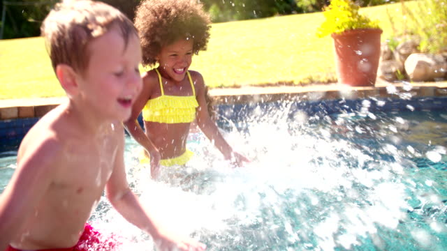 Laughing little Afro girl splashing with friends in a pool video