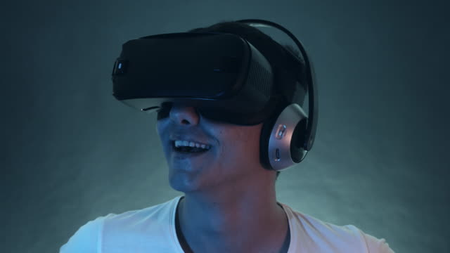 Laughing Young Man Wearing VR Headset And Experiencing Virtual Reality video