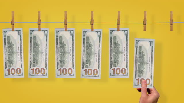 $100 Launder line conveyor, back side of $100 dollar bills on yellow background