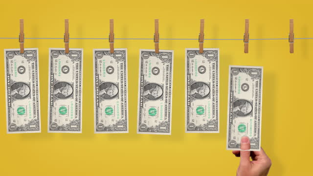 $1 Launder line conveyor, front side of $1 dollar bills on yellow background