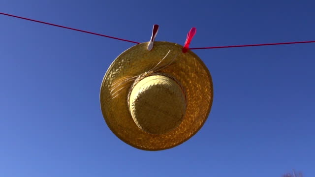 laundry clothes line with woman straw summer hat in wind video