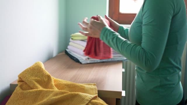 laundry day - woman folding washed towels - pranie filmów i materiałów b-roll