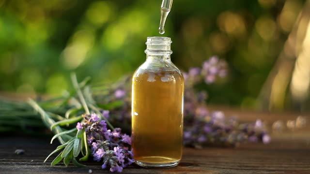 vídeos de stock e filmes b-roll de lavender essential oil in  beautiful bottle on table - fitoterapia