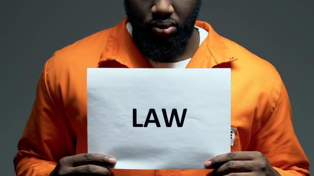 Law word on cardboard in hands of black prisoner, order and justice demanding Law word on cardboard in hands of black prisoner, order and justice demanding civil rights stock videos & royalty-free footage