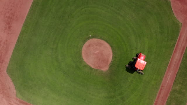Lawn mower is working on baseball green field. Camera is rotating around.