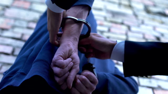 Lawyer arresting criminal, putting handcuffs on, law and order, crime punishment video