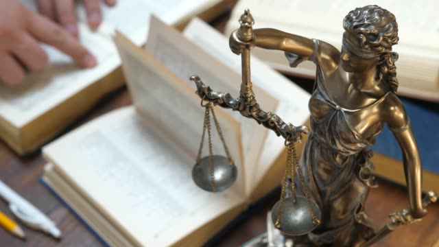 Lawyer Working with Ppapers and Law Books in Courtroom or Office The Statue of Justice. Lawyer working with papers and law books in courtroom or office. Concept of attorney or court judge, justice and law legal trial stock videos & royalty-free footage