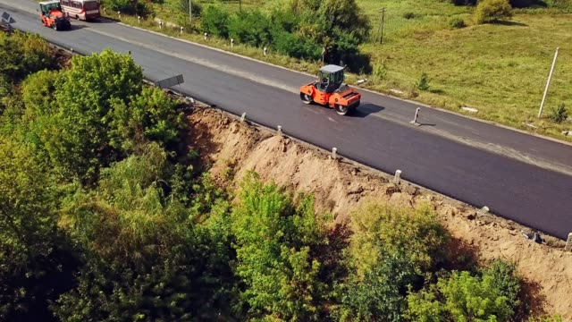 Laying a new asphalt on the road. Aerial view. Laying a new asphalt on the road. Road repair machine with heavy vibration roller compactor asphalt stock videos & royalty-free footage