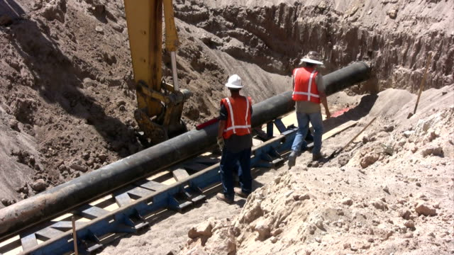 Laying a Pipeline Men in a work zone laying a pipeline.  gas pipe stock videos & royalty-free footage
