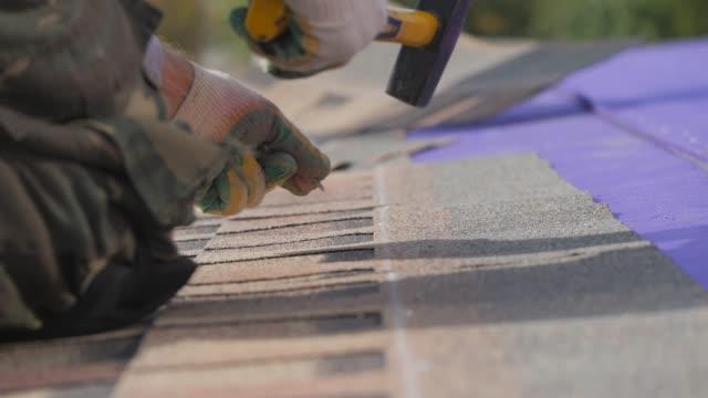 vídeos de stock, filmes e b-roll de colocando um telhado macio. trabalhe em altura. fixação de uma folha de material por meio de pregos e um martelo. - consertar