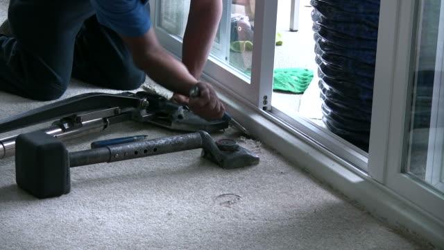 (hd1080i) posa tappeto, utilizzando scalpello a tappeto elastico in angolo - moquette video stock e b–roll