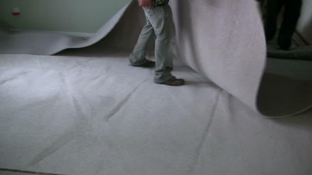 (hd1080i) sdraiati nuovi tappeti sul pavimento - moquette video stock e b–roll
