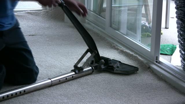 (hd1080i) sdraiati nuovi tappeti, stretching per adattarsi al piano terra - moquette video stock e b–roll