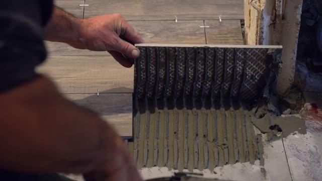 vídeos de stock e filmes b-roll de laying tile on the floor - concrete wall interior