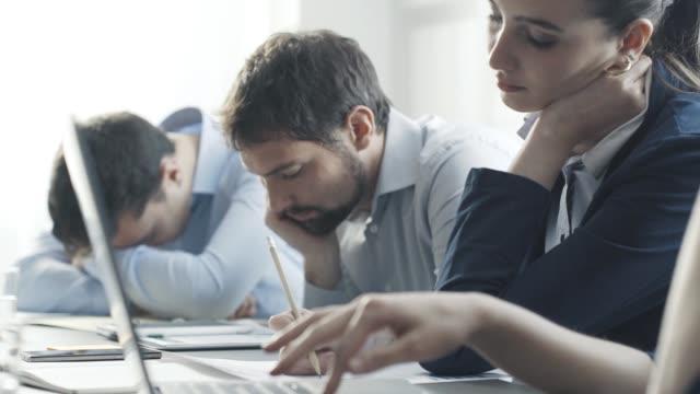 leniwi znudzeni bezproduktywnymi pracownikami w biurze - nuda filmów i materiałów b-roll