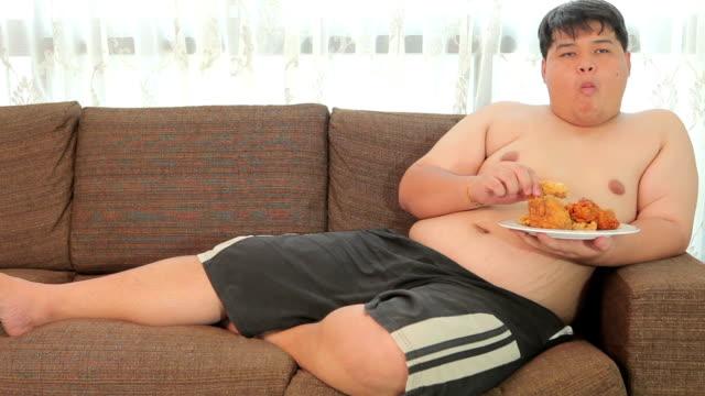 vídeos de stock, filmes e b-roll de preguiçoso homem asiático com excesso de peso com fast food e ver televisão - junk food