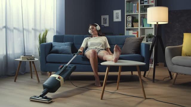 vídeos de stock e filmes b-roll de lazy woman sitting on the sofa and vacuuming the floor - lento