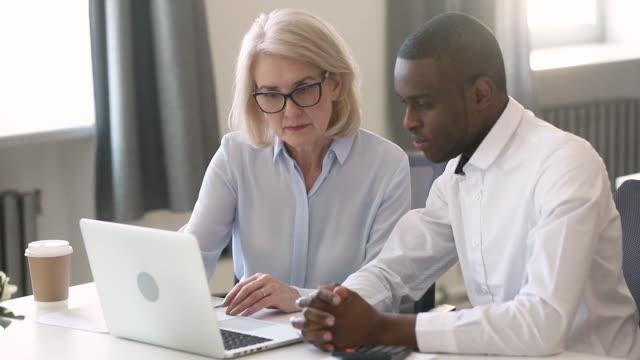 stockvideo's en b-roll-footage met leider van project leeftijd onderneemster legt details uit aan afrikaanse werknemer - omgeving