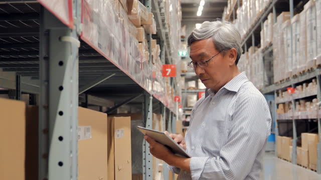 Leadership asian senior men age 62 year old working on a digital tablet in warehouse.Senior Technology concept. video