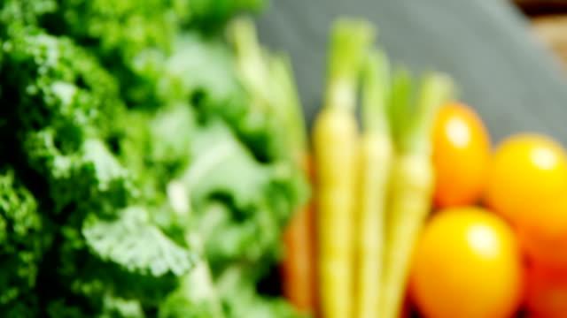 vídeos de stock, filmes e b-roll de vegetais folhosos com cenouras e tomates na mesa de madeira 4k - legume