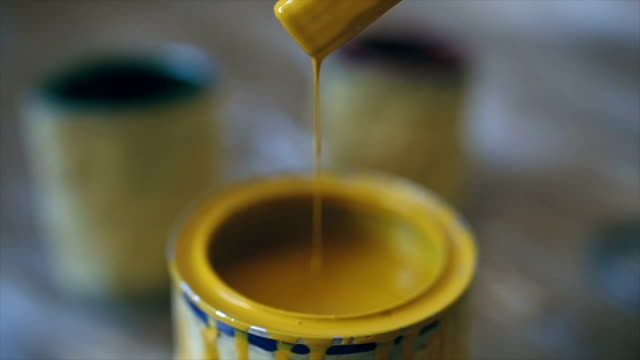 Leaking yellow paint View of paint cans  on the floor,yellow color paintbrush stock videos & royalty-free footage
