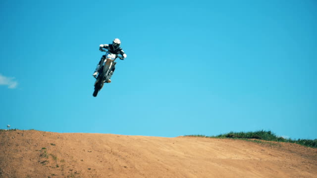 a leap of a motorcycler on his bike across dusty terrain - freestyle motocross video stock e b–roll