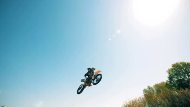 a leap of a motorcycle's driver against the sky in the background - supercross video stock e b–roll