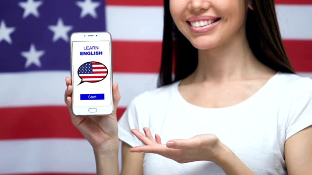 Learn English language app on cellphone in female hand, USA flag on background
