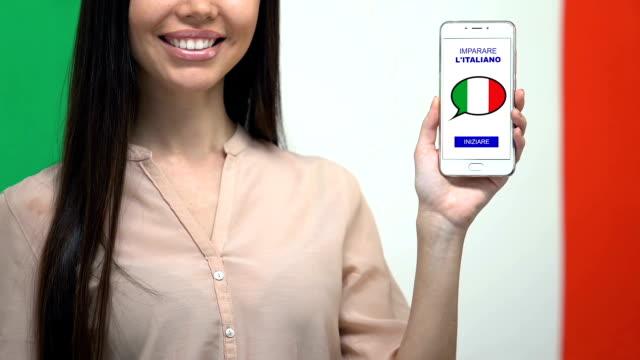 Learn Italian language app on smartphone screen in female hand, online education