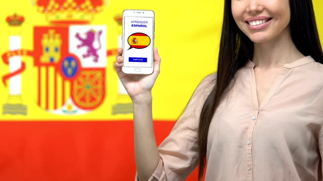 Learn Spanish language app on smartphone screen in female hand, online education