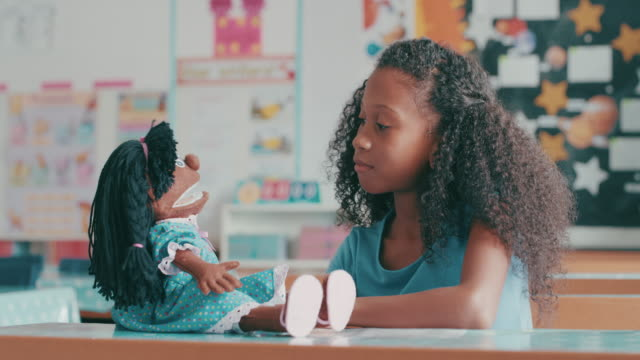 Learning about the importance of love 4k video footage of a young girl playing with a doll in a classroom at school doll stock videos & royalty-free footage