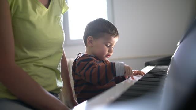 vídeos y material grabado en eventos de stock de aprender a tocar el piano - madre e hijos