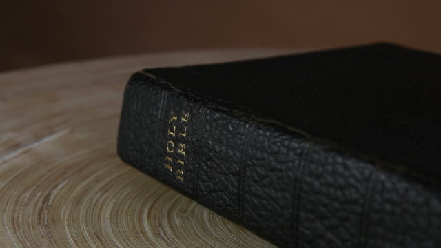 Leather Bound Holy Bible. An old leather bound holy Bible. Rotating into view on a round wooden desk top. old testament stock videos & royalty-free footage