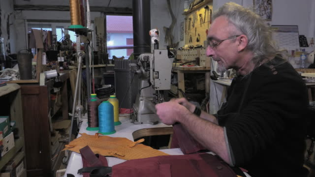 towarach skórzanych artisan w pracy w jego warsztatu - opalenizna filmów i materiałów b-roll