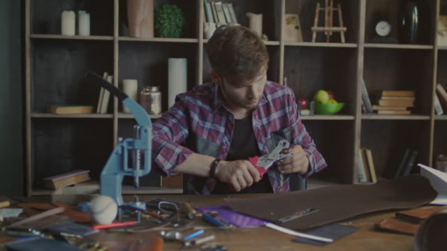 Leather manufacturer making metal clasp on leather strap. Small business video