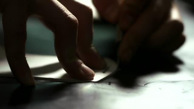 stockvideo's en b-roll-footage met lederen patroon snijden. close-up van leatherworker handen snijden van leder - dierenhuid huid