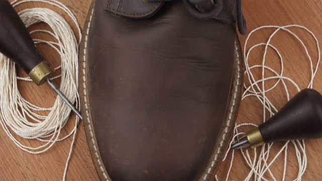 Leather shoes,  awl and thread, shoe repair