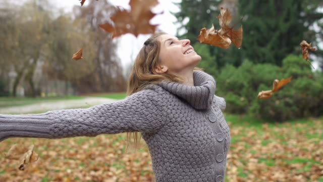 Leaves falling on girl while spinning and having fun video
