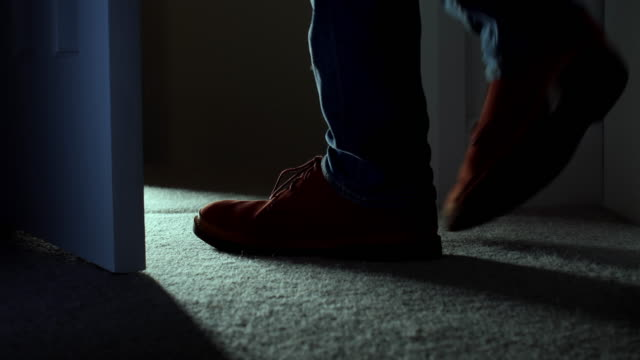 Leaving a dark room, close up of man's feet. DS.