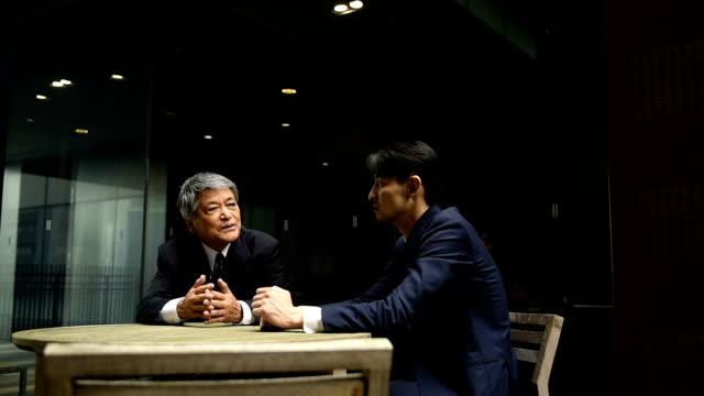 vidéos et rushes de à gauche de casserole hommes d'affaires parler - seulement des japonais