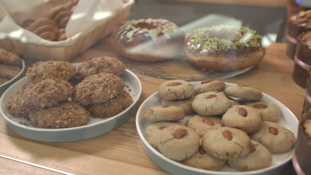 left to right shot of a sweet bakery products. brioche, panettone, oatmeal raisin cookie, chinese almond cookies. close-up demonstration video - panettone video stock e b–roll