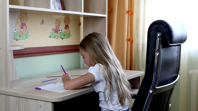 stockvideo's en b-roll-footage met linkshandige meisje zittend op een stoel door bureau tabel en schrijven door een pen in papieren notitieblok. terug naar school. kaukasische meisje glimlachend. zitten door tabel. schrijf met de pen. wit meisje schoolmeisje maken thuiswerk. - tienermeisjes