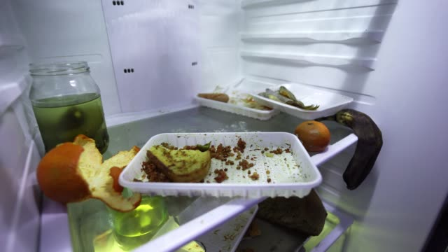 Leftover food in the fridge. Dirty refrigerator, inside view. Spoiled food.
