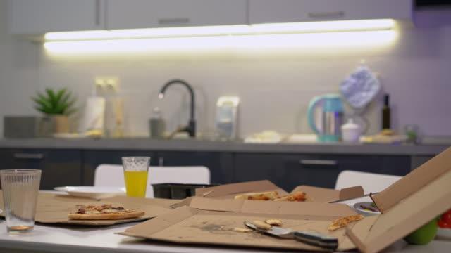 vídeos y material grabado en eventos de stock de pizza sobrante, cajas de cartón y vasos en la mesa, hogar sucio, limpieza - desordenado