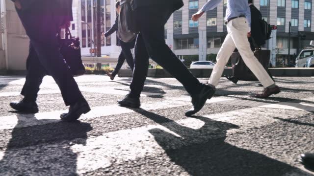 leg of business person attraversare la strada nel centro affollato - marciapiede video stock e b–roll
