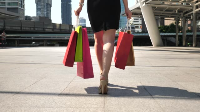 leg of woman walking with shopping bags - borsa della spesa video stock e b–roll