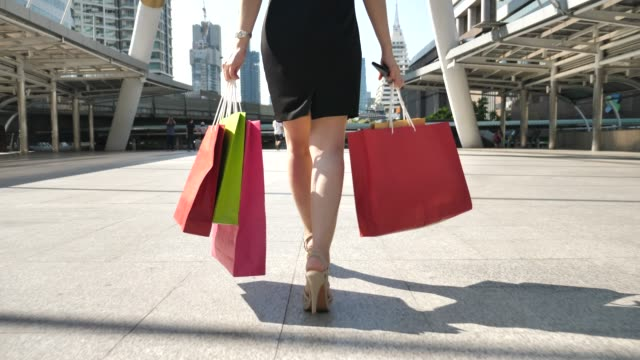 vídeos de stock, filmes e b-roll de perna de mulher jovem caminha com sacos de compras - salto alto